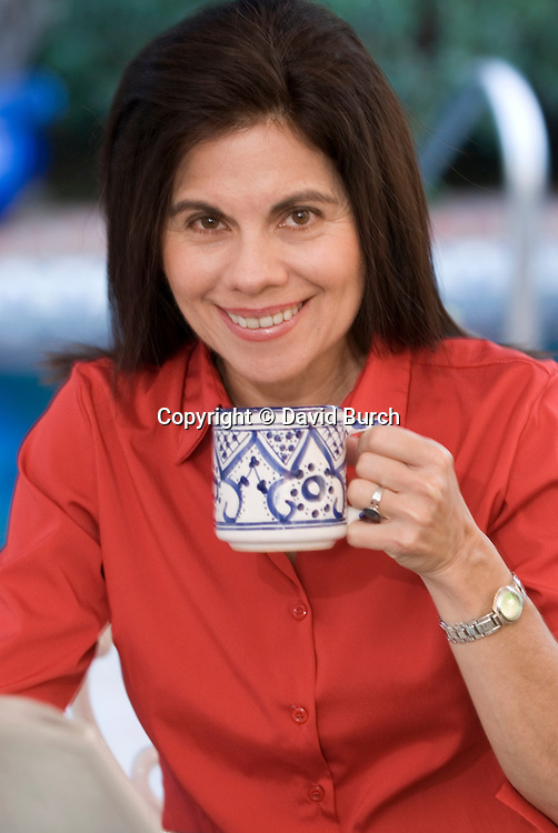 Hispanic woman smiling, drinking coffee