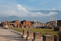 Forum, or civic centre of the city, 2nd century BC, Pompeii, surrounded by two-storey colonnaded porticoes with Doric columns. In the background Mount Vesuvius is obscured by clouds.