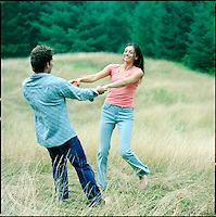 Couple, holding hands, playing in a field