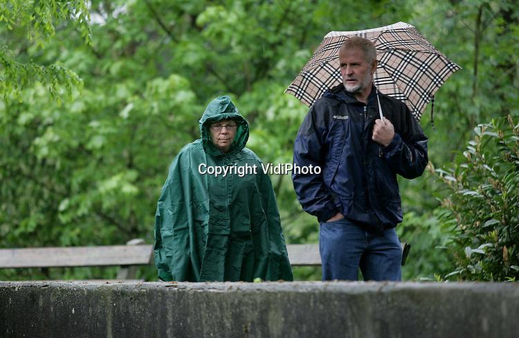 Foto: VidiPhoto..ARNHEM - Eindelijk regen. Na zes weken van droogte regent het weer eens flink. De verwachting is dat het de hele week vochtig blijft. Overigens niet tot vreugde van iedereen. De bezoekers van Burgers' Zoo in Arnhem waren er maandag minder blij mee.