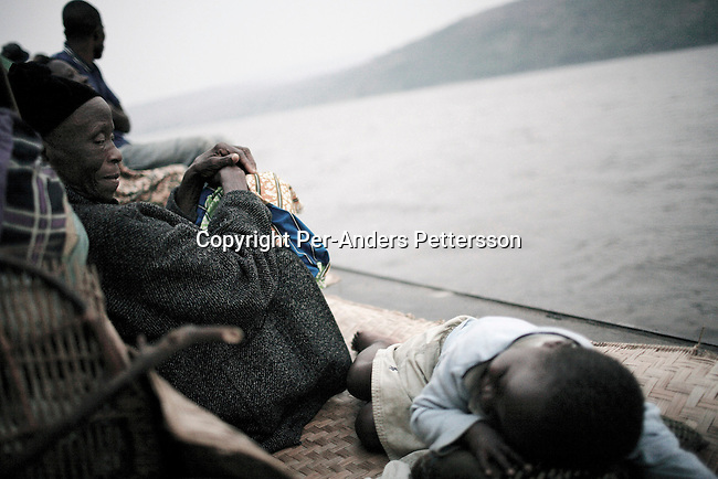 MALUKU, DEMOCRATIC REPUBLIC OF CONGO JULY 2: Lucie Malibua, age 68, wathes her granddaughter Sarah, age 5, as she tries to sleep while traveling on a boat made of big trees on the Congo River on July 2, 2006 outside Maluku, Congo, DRC. The boat traveled with about 150 passengers from Bumba to Kinshasa, a journey of about 1300 kilometers. The Congo River is a lifeline for millions of people, who depend on it for transport and trade. Passengers slept in the open, with their goats, pigs and other animals. Boat travel is the only option for most people along the river as there?s no roads or infrastructure. Very few can afford to fly in a plane to the capital Kinshasa. During the Mobuto era, big boats run by the state company ONATRA dominated the river. These boats had cabins and restaurants etc. All the boats are now private and are mainly barges that transport goods. The crews sell tickets to passengers who travel in very bad conditions. The conditions on the boats often resemble conditions in a refugee camp. Congo is planning to hold general elections by July 2006, the first democratic elections in forty years. The Congolese and the international community are hoping that Congo will finally have piece and the country will be rebuilt. (Photo by Per-Anders Pettersson)..