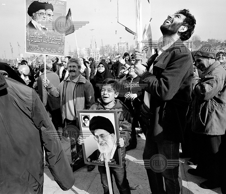 A young boy, his face painted with the Iranian flag, holds a picture of Ayatollah Ali Hosseini Khamenei as crowds of people enjoy the celebrations marking the 35th anniversary of the Iranian Revolution.