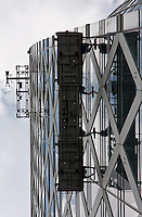 Window cleaners in a cradle on the Cocoon building in Shinjuku, Tokyo, Japan Friday May 28th 2010