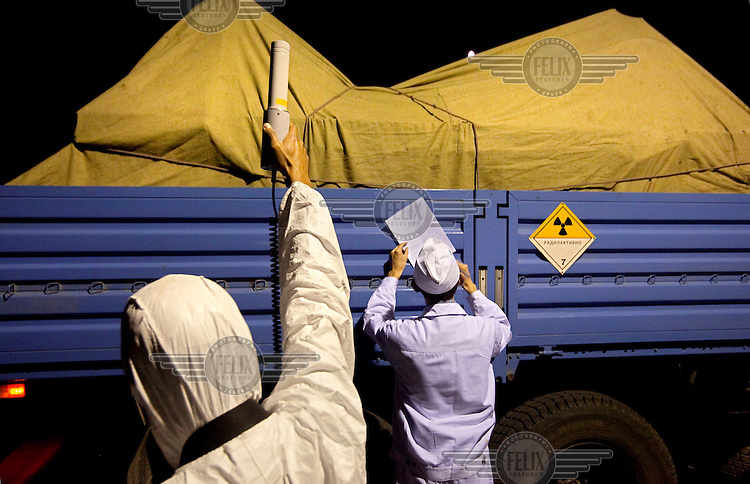 Technicians with a disometer monitor radioactivity as they transport highly enriched uranium (HEU) from the Institute of Nuclear Physics in Almaty. The removal of Kazakhstan's HEU is part of the U.S. Global Threat Reduction Initiative (GTRI) which tries to secure nuclear material around the world to prevent their misuse.