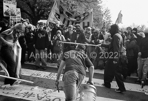 Washington DC.USA<br /> October 25, 2003<br /> <br /> Anti-War - Iraqi War demonstration in Washington DC attended by 50,000 people and a number of small groups of Pro-War - Bush counter demonstrators.<br /> <br /> Anti-war demostrators burn an American flag.
