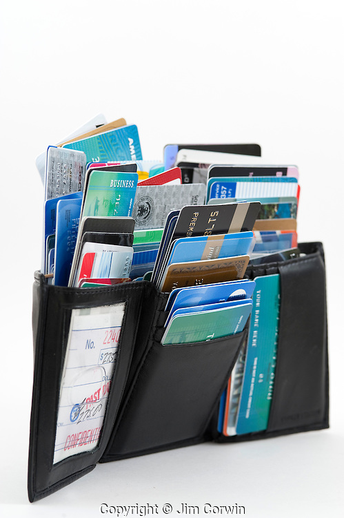 Wallet stuffed with credit cards on a white background studio image