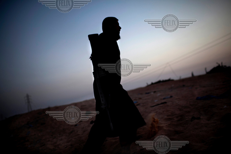 A rebel carries a gun as he walks towards the frontline. NATO airstrikes enabled the rebels to retake the city of Ajdabiya. On 17 February 2011 Libya saw the beginnings of a revolution against the 41 year regime of Col Muammar Gaddafi.