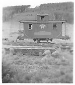 RGS caboose #0409 on blocks with no trucks still decorated for the movie &quot;Ticket to Tomahawk.&quot;<br /> RGS  Dallas Divide, CO  1953