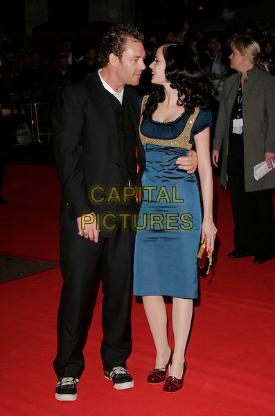 """EVA GREEN & GUEST .Attends the screening of """"Franklyn"""" at The Times BFI London Film Festival at Odeon West End, London, England, October 16, 2008..full length blue teal silk satin dress red purse clutch bag shoes profiles looking at each other .CAP/AH.©Adam Houghton/Capital Pictures"""