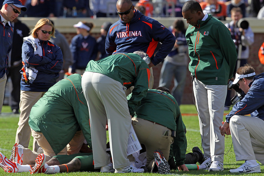 Oct 30, 2010; Charlottesville, VA, USA;   Miami Hurricanes head coach Randy Shannon, right,  and Virginia Cavaliers head coach Mike London, 2nd from right, watch as medical staff attend to Miami Hurricanes quarterback Jacory Harris (12) during the 1st half of the game at Scott Stadium.  Mandatory Credit: Andrew Shurtleff