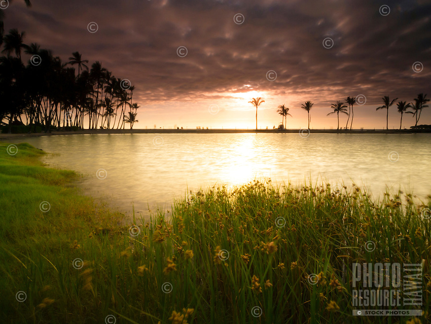 Sunset viewed from the back of the Ku'uali'i fishpond at 'Anaeho'omalu beach park, with 'Anaeho'omalu Bay in the distance, Island of Hawai'i.