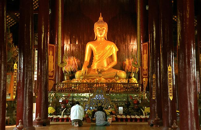 Worshipping Sukhothai style Sitting Buddha