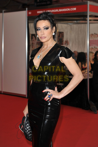 Nancy Dell'Olio.'Erotica' Exhibition at Olympia Hall, Kensington, London, England, UK, .18th November 2011..half length dominatrix black pvc shiny dress spider necklace hand on hip  blue ring .CAP/MAR.© Martin Harris/Capital Pictures.