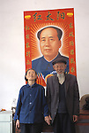 An indoor portrait of a senior Chinese couple in front of a poster of Chairman Mao near Zigui China
