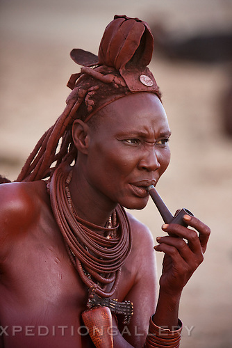 A Himba woman with a traditional leather headress and ochre covered hair braids smoking her pipe. Himba women cover their bodies with a traditional mixture of ochre and butter fat giving their skin and hair a reddish coloration. Himba are nomadic herders of goats and cattle, living in the dry desert regions of northwestern Namibia and southern Angola. [NO MODEL RELEASE]