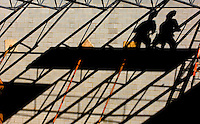 02/22/07:  Shadows of two construction workers are cast against a new cinderblock wall during construction/expansion of a Charlotte-area shopping center. Charlotte, NC, is one of the country's fastest-growing cities. ..By Patrick Schneider- Patrick Schneider Photography.