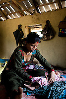 Nisha Darlami, 19, tends to her 1 month old baby girl, Bushpa, in her mother's house in Kalyan Village, Surkhet district, Western Nepal, on 30th June 2012. Nisha eloped with her step nephew when she was 13 but the couple used contraceptives for the next 6 years to delay pregnancy until she turned 18. In Surkhet, StC partners with Safer Society, a local NGO which advocates for child rights and against child marriage. Photo by Suzanne Lee for Save The Children UK