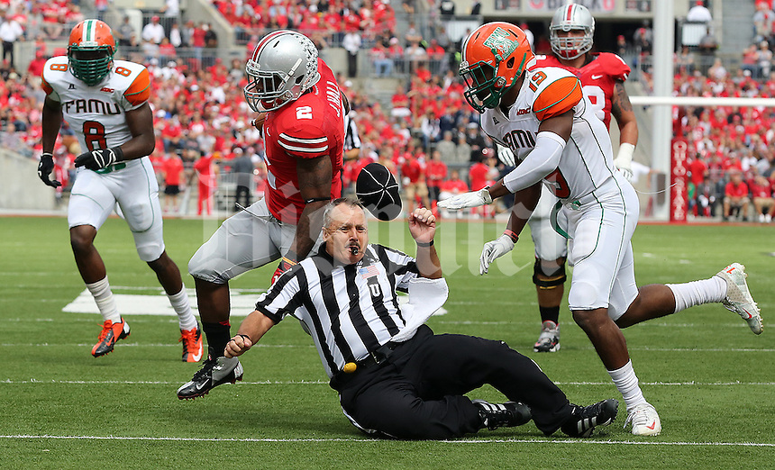 Ohio State Buckeyes running back Jordan Hall (2)  tackles umpire Jim Krogstad  alongside Florida A&M Rattlers defensive back Marshane Godbolt (15) in the second quarter of their NCAA football game at Ohio Stadium in Columbus, Ohio on September 21, 2013. (Columbus Dispatch photo by Brooke LaValley)