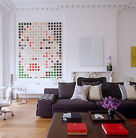 A large graphic painting by Sarah Morris hangs in one corner of the family room furnished with a Mister sofa by Philippe Starck and leather ottoman by Christian Liaigre