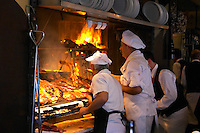 The gigantic huge charcoal grill with pieces of meat being cooked, several chefs cooks in white with a grilling fork, fire burning, in the restaurant El Palenque, the sword fish swordfish, in the Mercado del Puerto, the market in the port harbour harbor where many people go and eat and shop on weekends Montevideo, Uruguay, South America