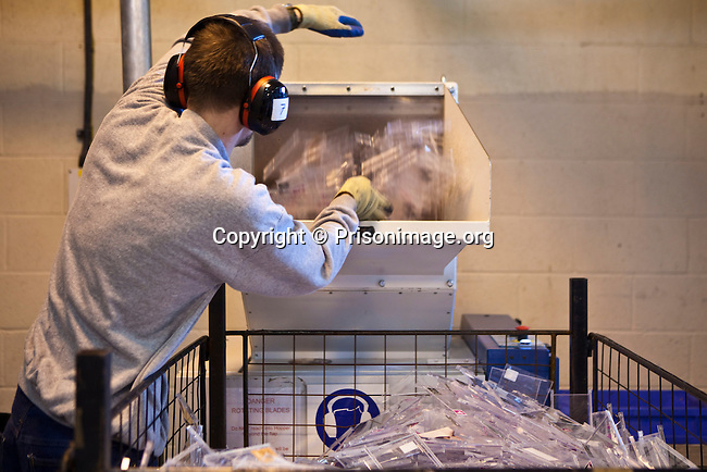 Recylcing plastic CD cases in the recylcing centre at HMP & YOI Littlehey. Littlehey is a purpose build category C prison.