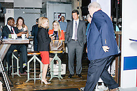 """Jay Faison, Founder and CEO of ClearPath Foundation (standing, center right) waits to be introduced before speaking on a panel put on by the Washington Post called """"Party Platform: Energy and Environment,"""" at Butcher and the Brewer outside the Republican National Convention in Cleveland, Ohio, on Tues., July 19, 2016. Former Mississippi Governor Haley Barbour leaves the stage (right) after an interview. Rep. Marsha Blackburn (R-Tenn.) (standing, center left) also spoke on the panel with Faison."""