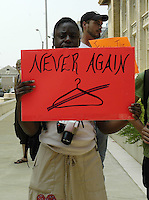"A young black woman holds a sign saying ""Never Again with a coat hanger "" on  it  outside the state capital in Jackson MS.members of the Pro-choice movement and NOW rally in response to the OSA campaign in Jackson MS. Operation Save America protest outside the only operating abortion clinic in jackson Mississippi Monday July 17,2006. Operation Save America is anti-abortion and plans to protest in jackson for as long as it takes to close the clinic, they are also planning protest at the state capital.(Photo©Suzi Altman)"