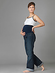 Pregnant young woman wearing maternity jeans with a stretch band around her belly