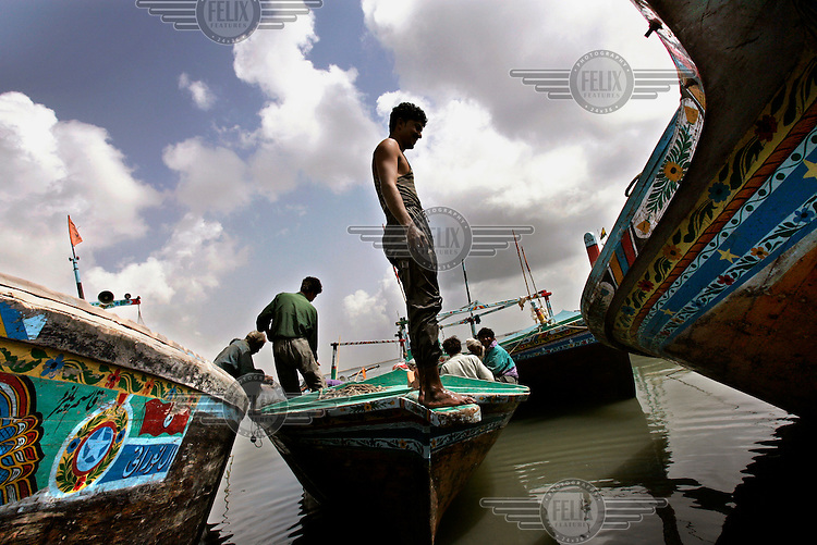 Fishermen tend to their fishing boats in Bin Qasim Town. Hundreds of local fishing communities in Pakistan are suffering hardship due to the presence of deep-sea trawlers from the Far East. The Pakistani government's policy of opening up its waters to transnational fleets and the liberalisation of the global fishing trade are depleting fish stocks and forcing local residents out of their traditional livelihoods.