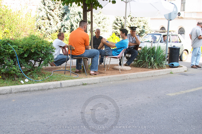 Parking guards and other people sitting loitering in the shade. Historic town of Mostar. Federation Bosne i Hercegovine. Bosnia Herzegovina, Europe.