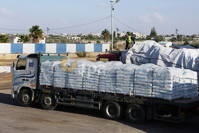 A Palestinian worker walks on top of a truck loaded with supplies that entered the Gaza Strip from Israel through the Kerem Shalom crossing in Rafah in the southern Gaza Strip on November 5, 2014. UN peace envoy Robert Serry announced on November 4 that the temporary reconstruction mechanism for the war-torn Palestinian territory had begun operations, under the auspices of the newly formed Palestinian unity government, noting the urgency in providing cement and other materials to tens of thousands of damaged homes in Gaza ahead of winter. Photo by Abed Rahim Khatib