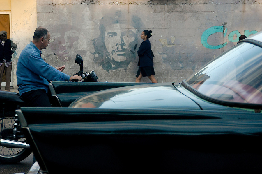 A painted graphic of the revolutionary Che Guevara marks a wall as locals pass by in Havana, Havana Province of Cuba, on Jan. 16, 2004.