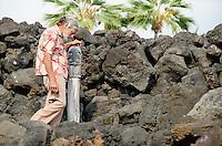 Artist Geno Bergmann near a carved wooden statue he created many years ago for Kealakowa'a Heiau in Kailua-Kona, Big Island.