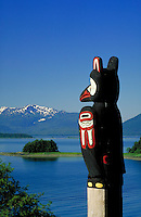 A totem pole marks the original winter village site of the Auk-kwan Tlingit Indians in Juneau, Alaska.  Looking out over Auke Bay and the Tongass National Forest in Southeast Alaska, the Yax Te pole was carved in 1941 by Frank St. Clair. Juneau Alaska, Au