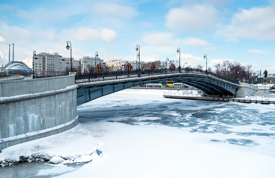 View of one of the many bridges crossing the Moskva River in Moscow, during winter time with a frozen river.