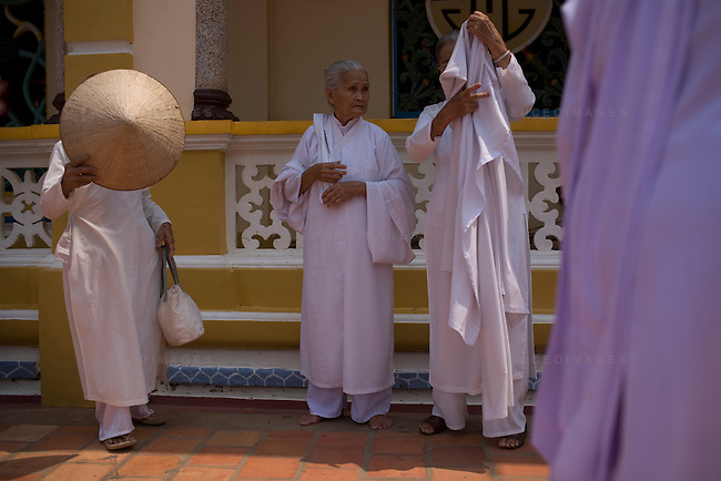 Followers of the Cao Dai religion wait for the daily ceremony to begin in Tay Ninh, Vietnam.