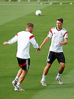 Mesut Ozil and Lukas Podolski of Germany warming up during training