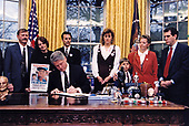 United States President Bill Clinton signs a Memorandum directing the heads of Executive Departments and Agencies to designate an area in all federal buildings for the posting of missing children notices in the Oval Office of the White House in Washington, DC on January 19, 1996.  The President was joined at the signing in the Oval Office by Americans who have been the victim of this tragedy, including (left to right): Don and Claudine Ryce, Marc Klaas, Colleen Nick, Adam Croote, and Linda Koerner. Standing far right is US Representative Peter Deutsch (Democrat of Florida).<br /> Mandatory Credit: Sharon Farmer / White House via CNP
