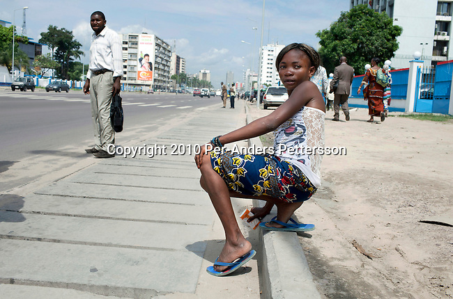 KINSHASA, DRC - NOVEMBER 2: Esther Yandakwa, a 13-year old homeless child sits on the pavement on the streets of Kinshasa DRC. She has lived on the streets since she was 6-7 years old and is dependent on prostitution to survive. She is walking the streets of Kinshasa to look for customers. She uses drugs and lives with a group of other homeless people in central Kinshasa. Thousands of children live on the streets of Kinshasa. Esther has been in and out orphanages or but she is only happy living in the mean streets of Kinshasa. (Photo by: Per-Anders Pettersson)