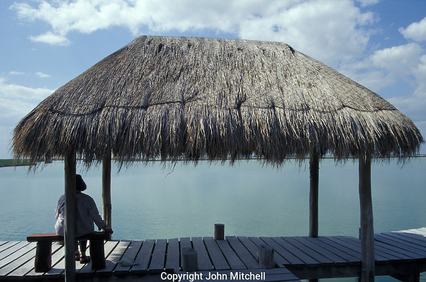 Tourist sitting under a palapa next to a lagoon in Sian Ka'an Biosphere Reserve, Quintana Roo, Mexico