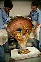 Nutty Turkish Delight mixture is poured from a copper vat into a tray ready for setting by two workers. When the mixture has set it will cut into the classic cube shapes and sold in the sweet shop below.