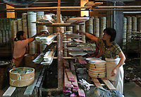 A Chinese worker places clay wares into oven molds at the Guangming Porcelain Factory in Jingdezhen, Jiangxi Province, China. The township of Jingdezhen is well known in China as the country's porcelain capital ever since it was selected exactly one thousand years ago as the royal porcelain provider for the imperial court..24-JUN-04