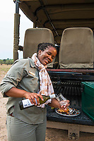 Africa, Botswana, Kasane, Chobe Game Lodge. Neo Moatshe, female guide, serving sundowner cocktails while on safari. Chobe Game Lodge has all women guides.