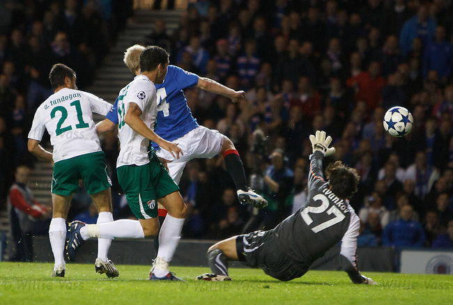 Sreven Naismith flicks the ball over Bursaspor keeper Dimitar Ivankov to open the scoring for Rangers