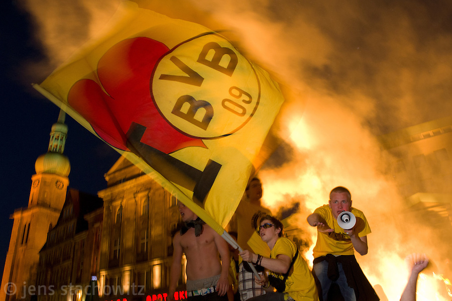 In the ancient marketplace in Dortmund fans celebrate a party because of the title win of their favorite soccer club BVB 09 in the German Premium League. Here they are waving a self sewed flag »I love BVB« and are  whipping up the masses to chant while bengal fireworks are displayed in the background.