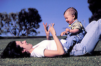 Mother, Christine, lying on her back with baby Alexander sitting on her stomach, playing, motherhood, babies, laughing, happy. Alexander and Mom. Santa Monica California.