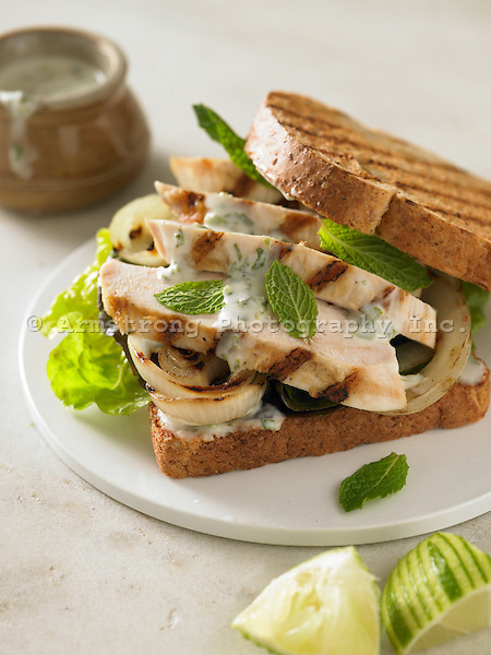 A sandwich on whole wheat bread with grilled chicken breast, grilled onion, yogurt sauce, lettuce, and fresh mint.