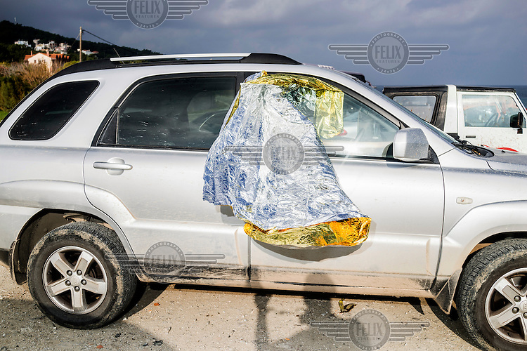 A reflective heat blanket hangs out the window of a volunteer's car.