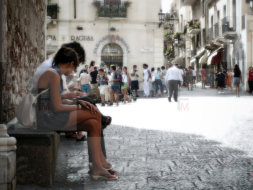A pair of tourists sitting reading the map in Piazza Duomo