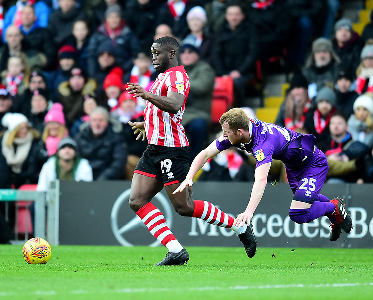 Lincoln City's John Akinde battles with  Grimsby Town's Alex Whitmore<br /> <br /> Photographer Andrew Vaughan/CameraSport<br /> <br /> The EFL Sky Bet League Two - Lincoln City v Grimsby Town - Saturday 19 January 2019 - Sincil Bank - Lincoln<br /> <br /> World Copyright &copy; 2019 CameraSport. All rights reserved. 43 Linden Ave. Countesthorpe. Leicester. England. LE8 5PG - Tel: +44 (0) 116 277 4147 - admin@camerasport.com - www.camerasport.com
